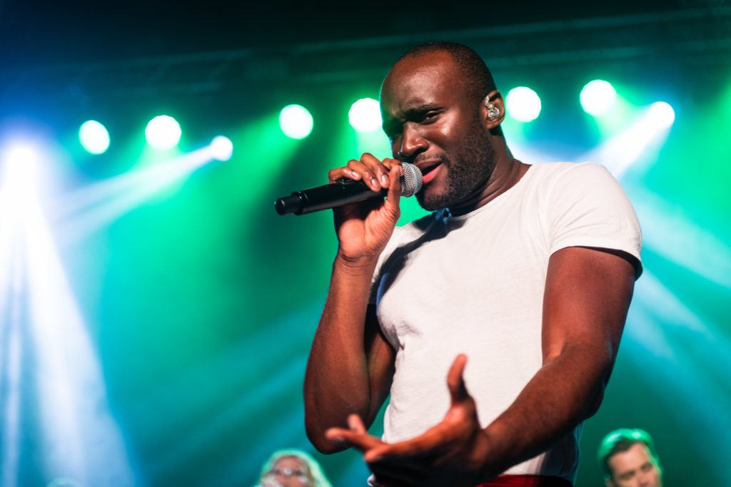 Manlig artist sjunger i mikrofon