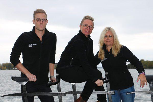 Tre anställda på Stadium Outlet poserar vid cykelstaty med vatten i bakgrunden