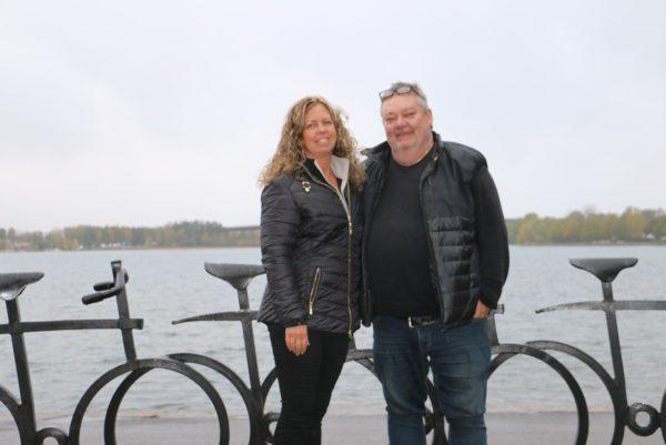 Två anställda på Blomsterglädje framför cykelstaty med vatten i bakgrunden