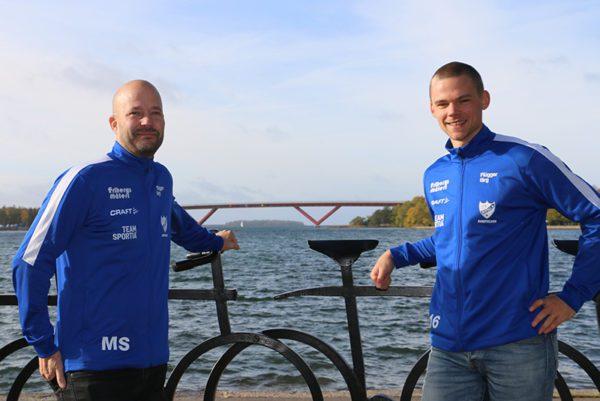 Två spelare från IFK Bandyn med Motalabron i bakgrunden