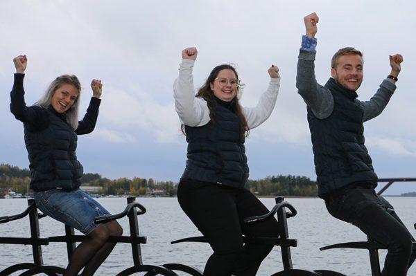 Tre anställda på Städarna i Motala lyfter armarna i luften