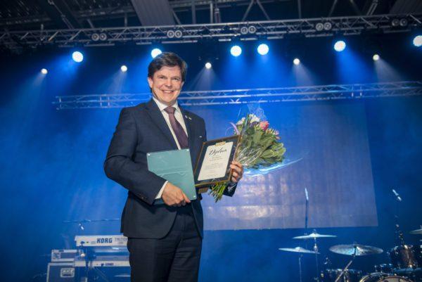 Man i kostym framför scenen med diplom och pris i händerna