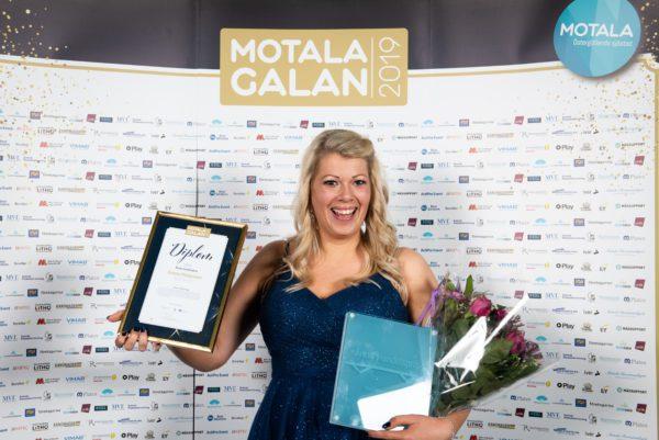 Glad kvinna framför fotovägg med diplom och pris i händerna