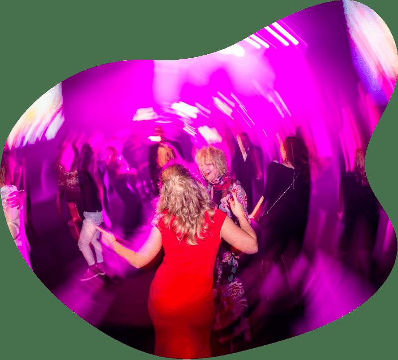 Kvinna i röd klänning dansar på dansgolv med ryggen mot kameran.